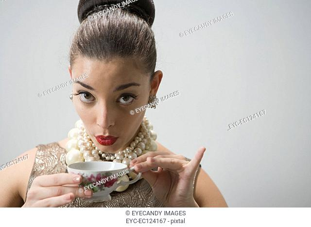 Young woman with pearls necklace wearing eye mask