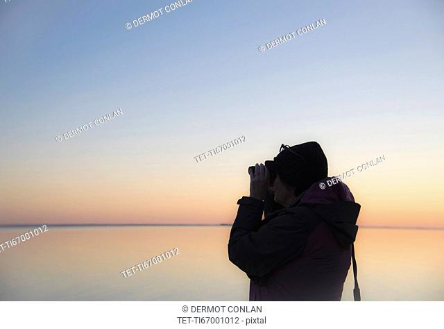 Senior woman birdwatching at sunset