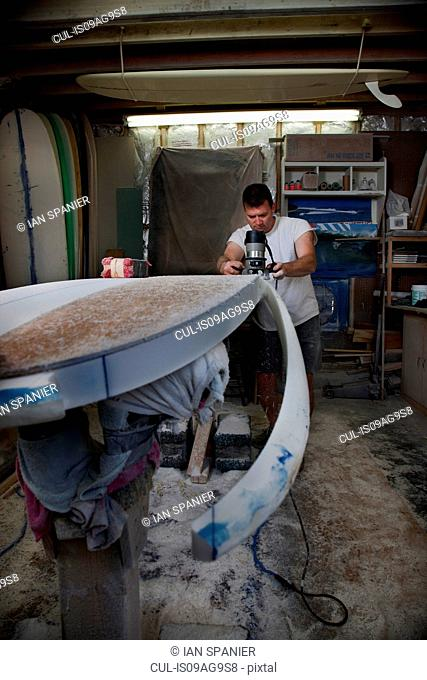 Mature man sawing a surfboard in his workshop