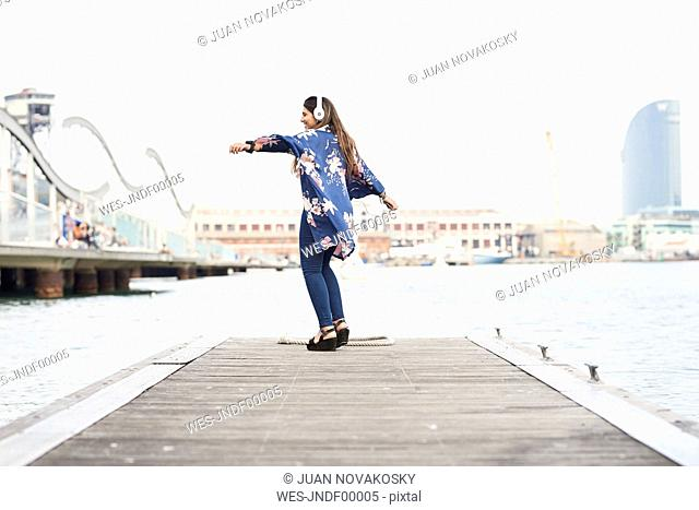 Spain, Barcelona, happy young woman with headphones dancing on jetty