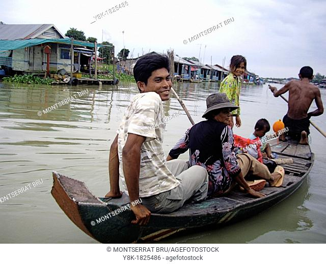 Cambodian family on a boat at Tonle Sap Lake with floating village in the background, Cambodia