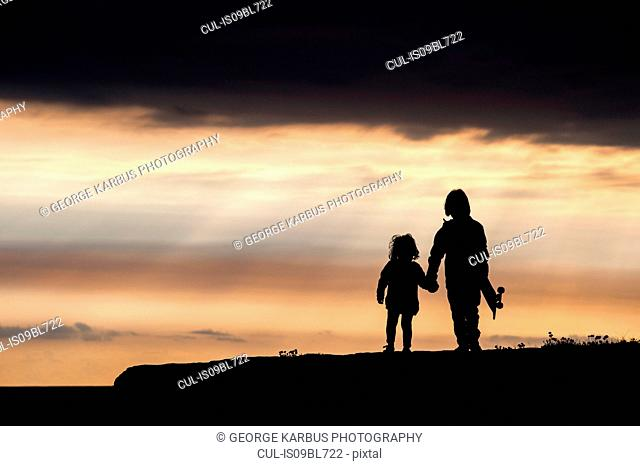 Brother and sister, walking hand in hand, at sunset, Doolin, Clare, Ireland