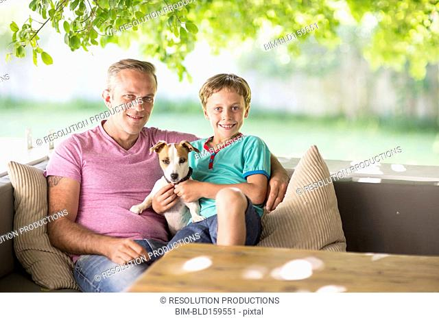 Caucasian father and son sitting with dog on sofa