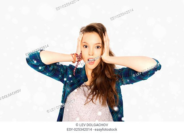 winter, christmas, people, hair care, style and teens concept - happy pretty teenage girl holding to head over gray background and snow