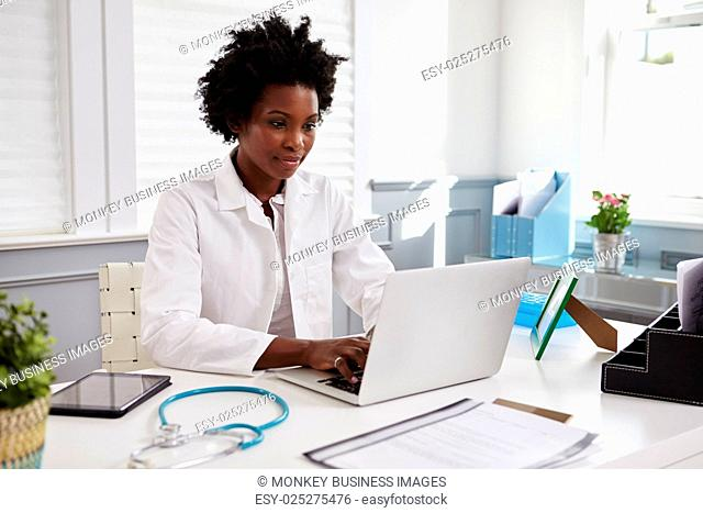 Black female doctor wearing white coat at work in an office
