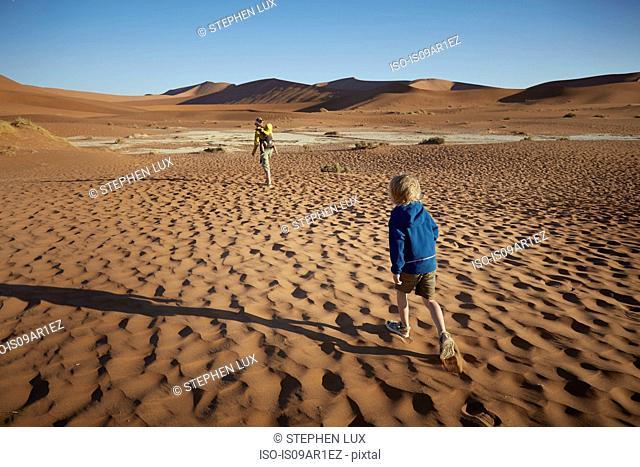 Boy walking in desert, Namib Naukluft National Park, Namib Desert, Sossusvlei, Dead Vlei, Africa