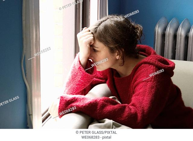 Young woman sitting next to a window