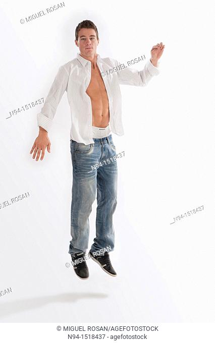 Full-body photograph of a teenage boy, jumping, with jeans and white shirt open