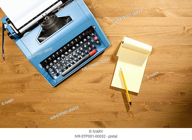 High Angle View Of The Type Writer With The Notepad And Paper Inside It