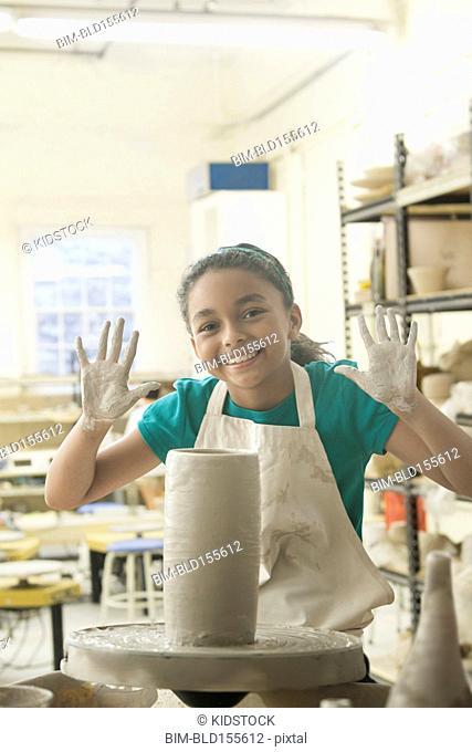 Mixed race girl showing hands near pottery wheel