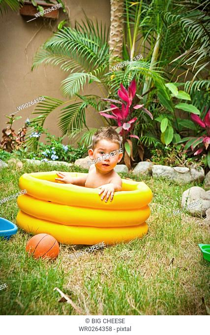 young boy playing in paddling pool