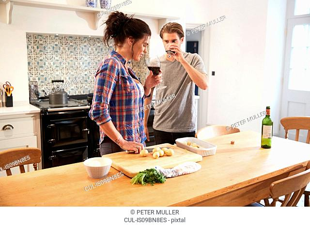 Couple preparing food and drinking wine at kitchen table