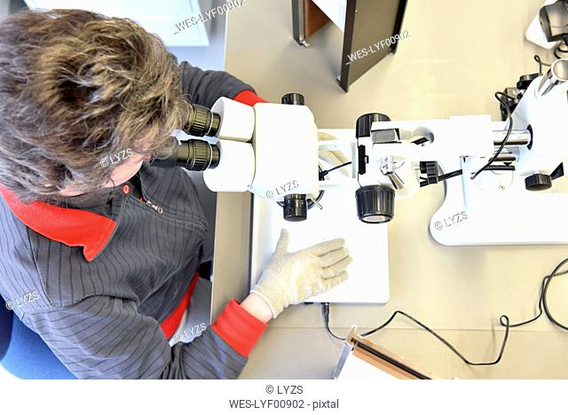 Woman using a microscope for the quality control in the manufacturing of ceramic circuit boards for the electronics industry