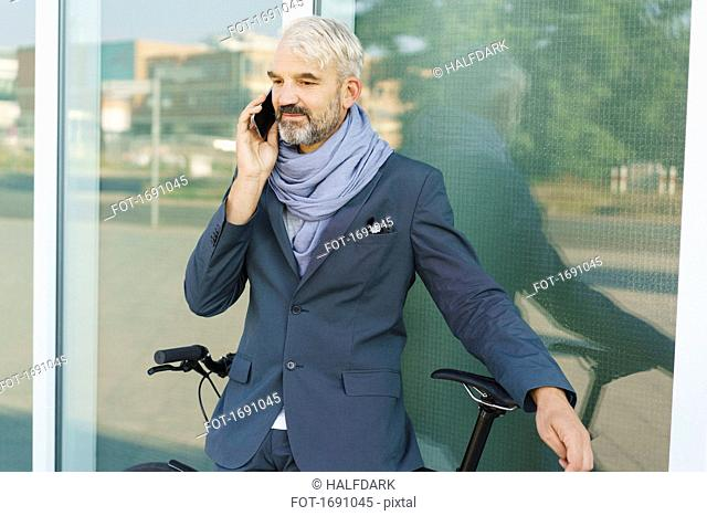 Confident businessman with bicycle talking on mobile phone while standing against glass building