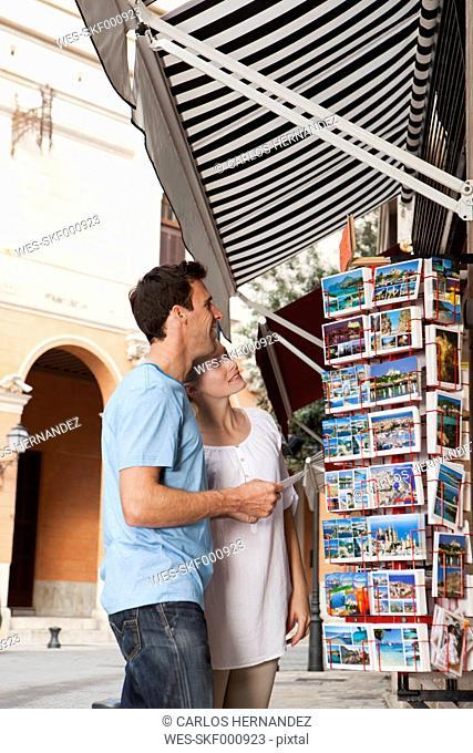 Spain, Mallorca, Palma, Couple looking at postcards, smiling
