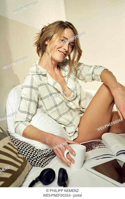 Portrait of smiling woman sitting on bed with coffee mug and magazine
