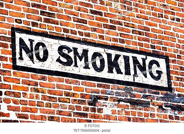 No smoking sign on red brick wall