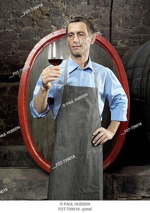 A vintner studying red wine in a glass