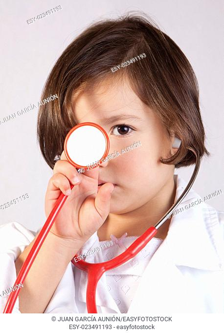 Little girl showing and playing with a stethoscope. Isolated over white background