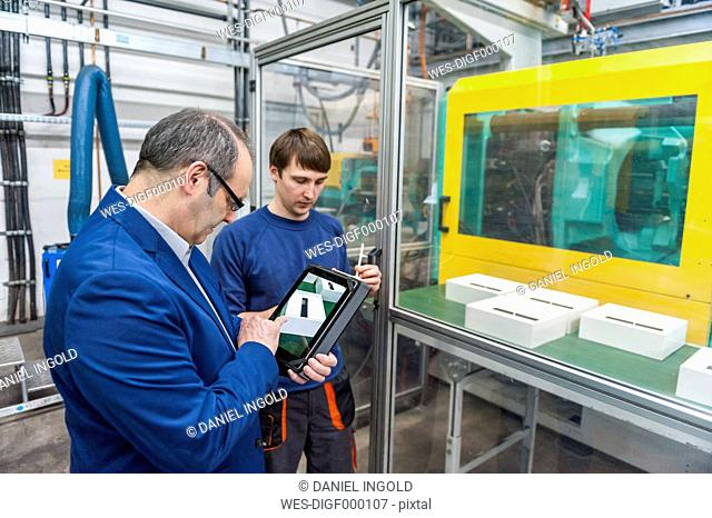 Manager and worker doing quality assessment in plastics factory
