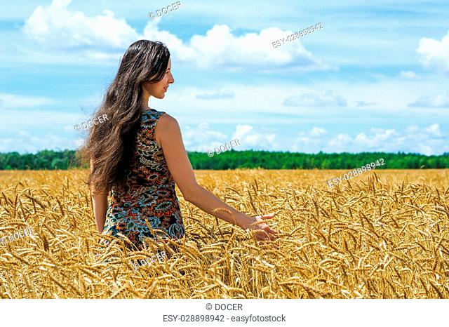 young woman standing and touch a wheat in cereals field