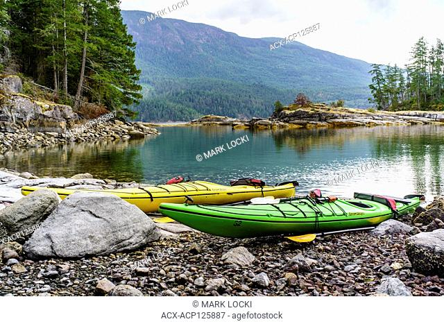 Two Kayaks along a shoreline in Desolation Sound, Sunshine Coast, British Columbia, Canada