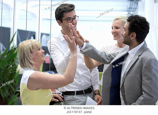 Businesspeople Celebrating In Office Meeting With High Five