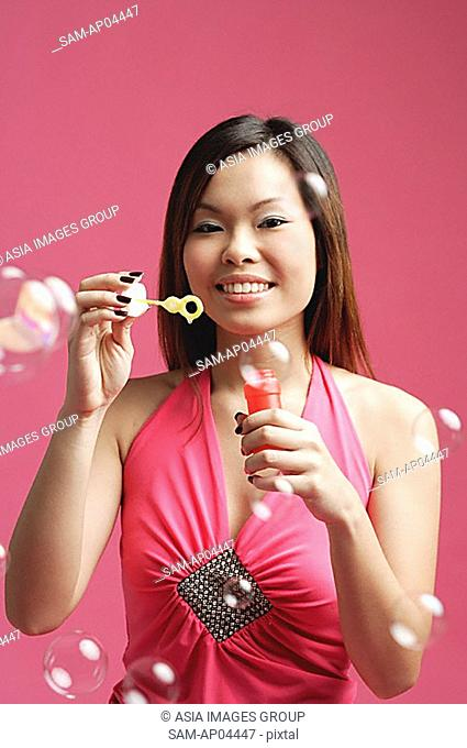 Woman dressed in pink, holding bubble wand