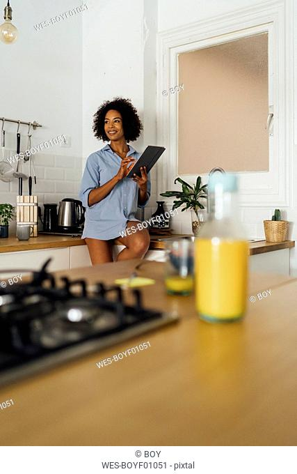 Woman sitting on worktop of her kitchen, using digital tablet in the morning