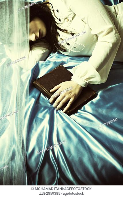 Sad young woman laying down in bed hand on book