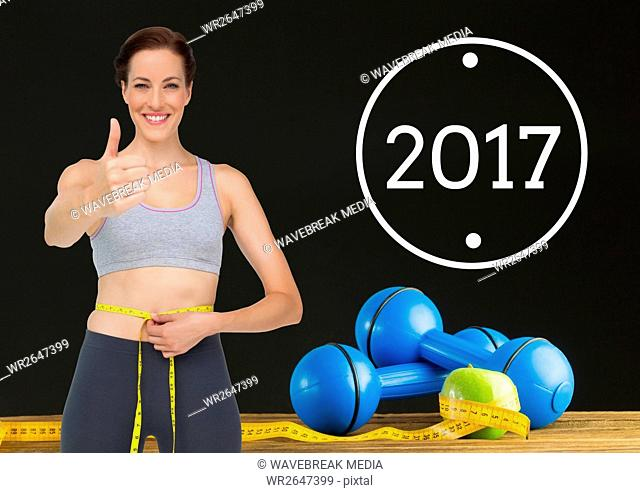 Woman measuring her waist against 2017and showing thumbs up