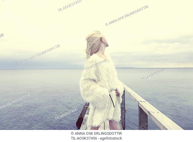 Female teenager with blonde hair standing by sea
