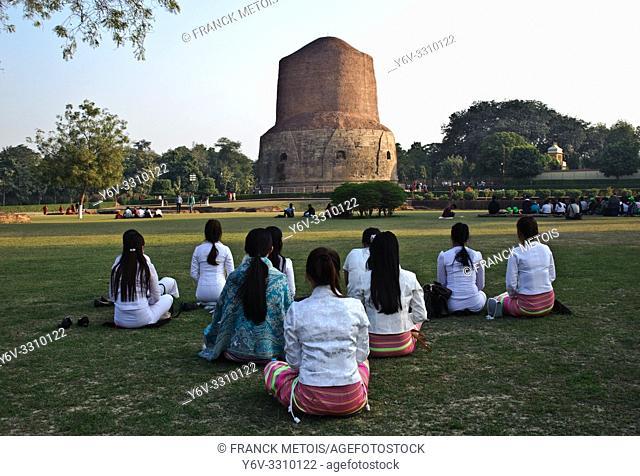 Buddhist young women meditating in front of Dhamek stupa ( Sarnath, India)