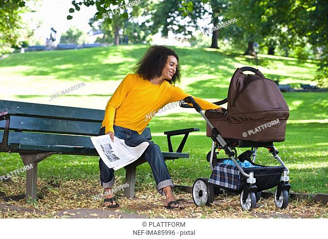 Smiling young man with baby carriage sitting on bench