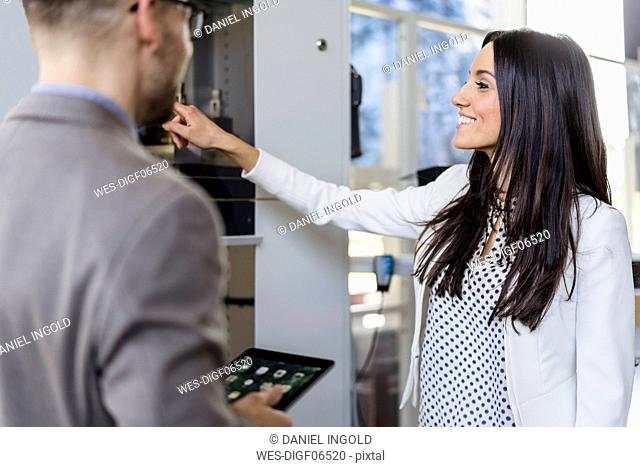 Businesswoman showing machine to businesman in a modern factory