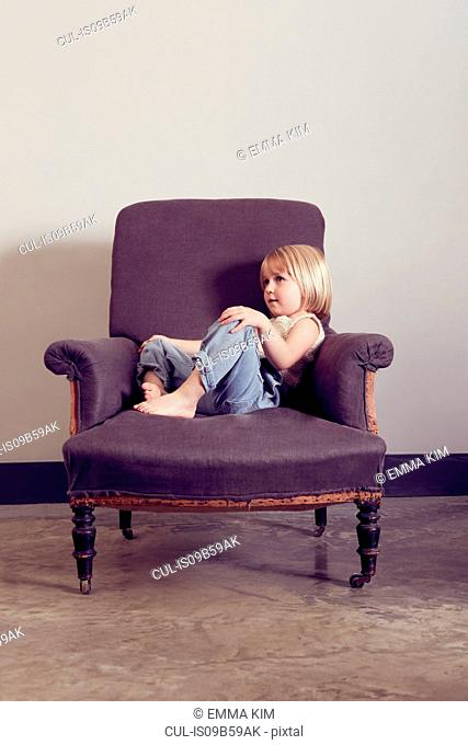 Girl reclining on vintage armchair gazing