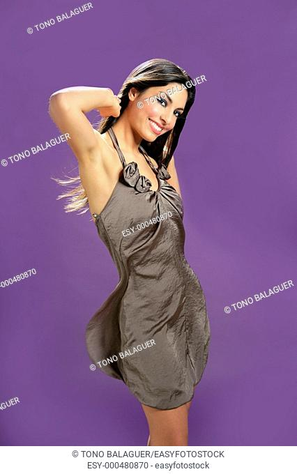 Brunette indian beautiful woman dancing at studio on purple background