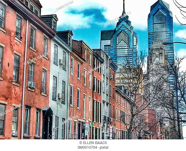 Modern buildings Liberty Place appearing above charming old brick apartment buildings on 16th Street in downtown Philadelphia in winter