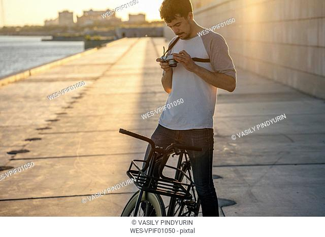 Young man with commuter fixie bike and camera on waterfront promenade at the riverside