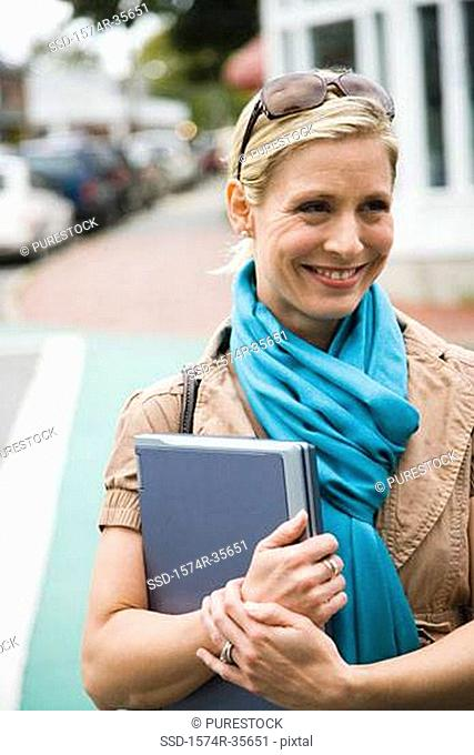 Close-up of woman holding laptop and smiling