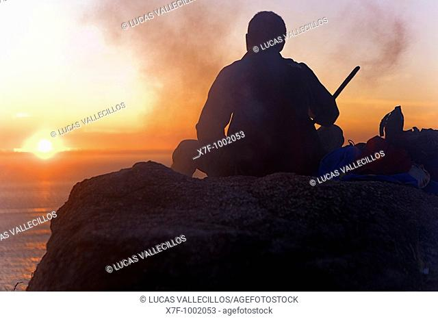 pilgrim enjoying a sunset in Cape Finisterre and burning the clothes used during the peregrination to Santiago de Compostela  Finisterre Coruña province Spain...