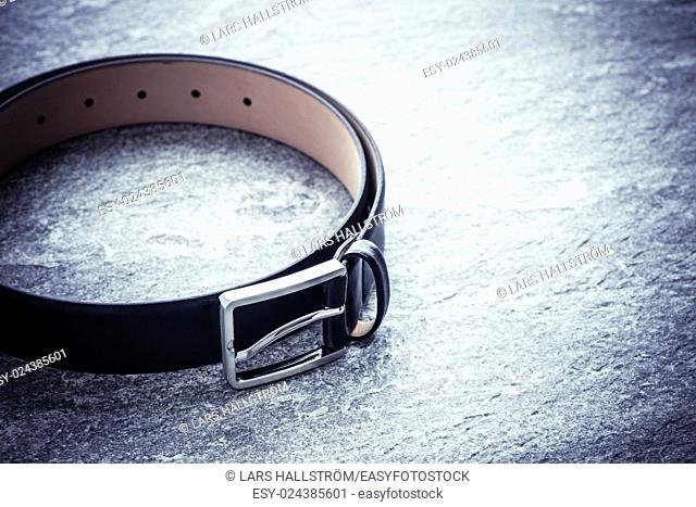 Black leather belt on stone surface. Still life image of clothes accessory