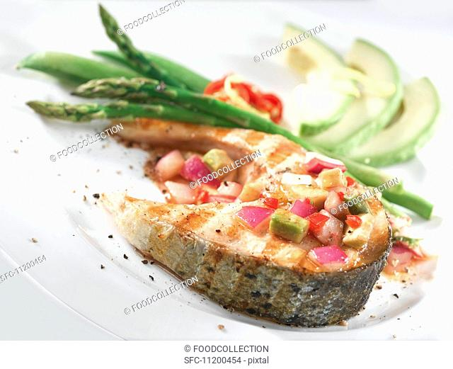 Salmon steak with avocado salsa and green asparagus