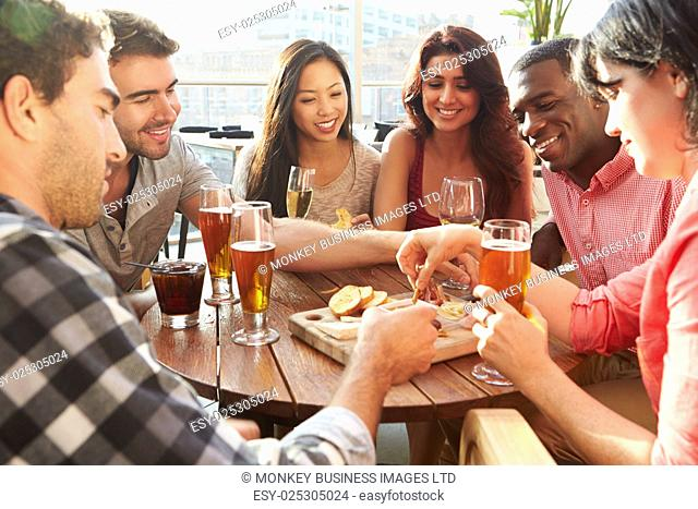 Group Of Friends Enjoying Drink And Snack In Rooftop Bar