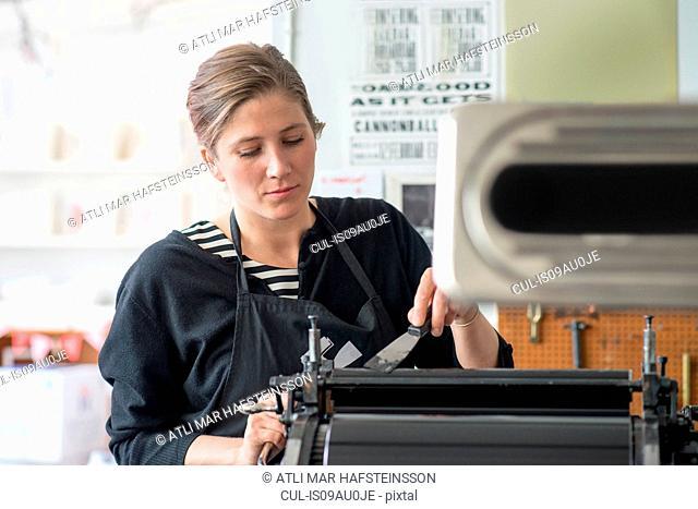 Female letterpress printer inking machine in workshop