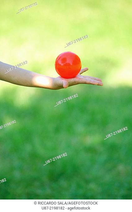 Teenage Boy Holding a Red Ball