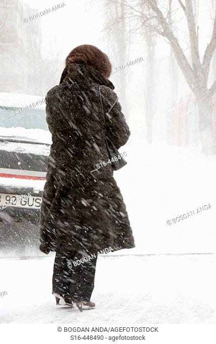 Woman standing in the street during a blizzard - Bucharest, Romania