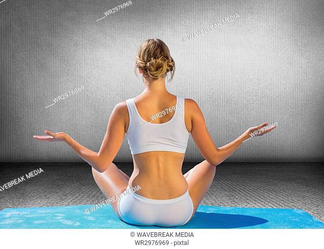 Back of woman meditating against grey wall