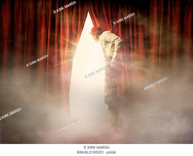 Caucasian man peering through red curtain