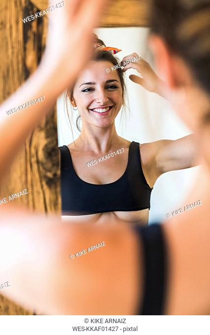Mirror image of smiling young woman wearing bra